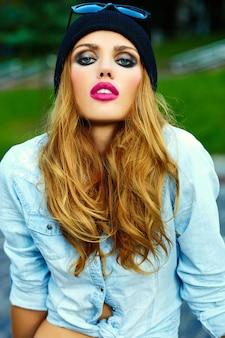 Wygląd mody. seksowny styl życia blond kobieta dziewczyna model w dorywczo jeansy spodenki tkaniny siedzi na zewnątrz na ulicy w czarnej czapce w okularach