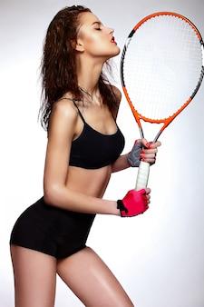 Wygląd mody. seksowny zbliżenie portret pięknej seksownej stylowej brunetki kaukaskiej młodej zawodowej modelki tenisistki z jasnym makijażem, z czerwonymi ustami z rakietą