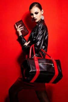 Wygląd mody. seksowny zbliżenie portret pięknej seksownej stylowej brunetki młodej kobiety rasy kaukaskiej model w czarnej kurtce z torbą jasny makijaż, z czerwonymi ustami, z idealnie czystą skórą w studio