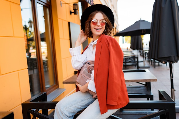 Wygląd mody ulicznej. niesamowita stylowa podróżująca dziewczyna w modnym jesiennym stroju pozuje na świeżym powietrzu
