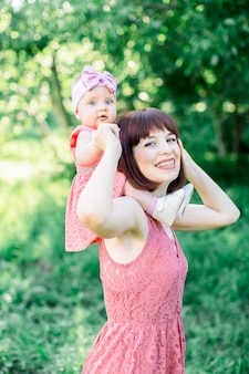 Wygląd rodziny. małe dziecko, mała dziewczynka siedzi na ramionach uśmiechniętej mamy