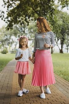 Wygląd rodziny. matka i córka ubrane w różowe spódnice i białe trampki, mając ładny, uroczy rodzinny wygląd