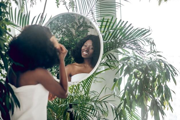 Wygląd zewnętrzny. odbicie w okrągłym lustrze ciemnoskórej uśmiechniętej młodej dorosłej kobiety z nagimi ramionami z grzebieniem