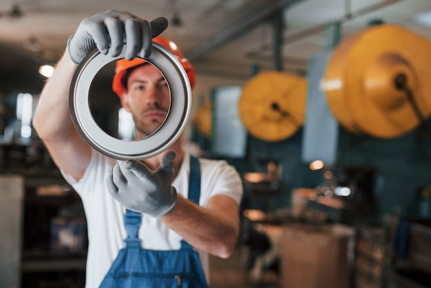 Wygląda dobrze. mężczyzna w mundurze pracuje nad produkcją. nowoczesna technologia przemysłowa.