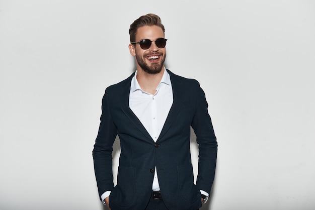 Wygląda Idealnie. Przystojny Młody Mężczyzna W Pełnym Garniturze, Trzymający Ręce W Kieszeniach I Odwracający Wzrok Z Uśmiechem, Stojąc Na Szarym Tle Premium Zdjęcia