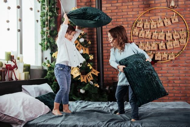 Wygląda na walkę na poduszki. wesołe dzieciaki bawią się i skaczą na łóżku