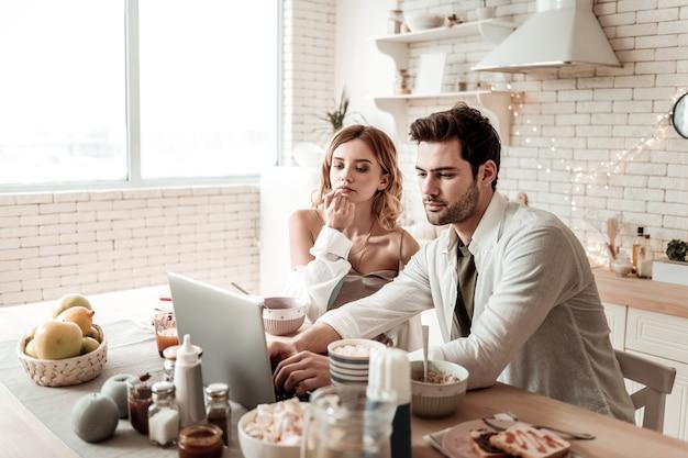 Wygląda na zaangażowanego. długowłosa, rozpromieniona ładna kobieta ubrana w domowe ciuchy wyglądająca na zaciekawioną podczas oglądania filmu z mężem