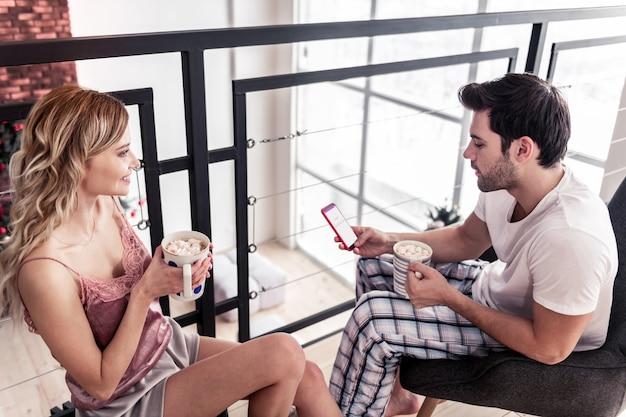 Wygląda na zainteresowanego. ciemnowłosy brodaty młody mężczyzna ubrany w białą koszulkę wygląda na skoncentrowanego, czytając coś w internecie