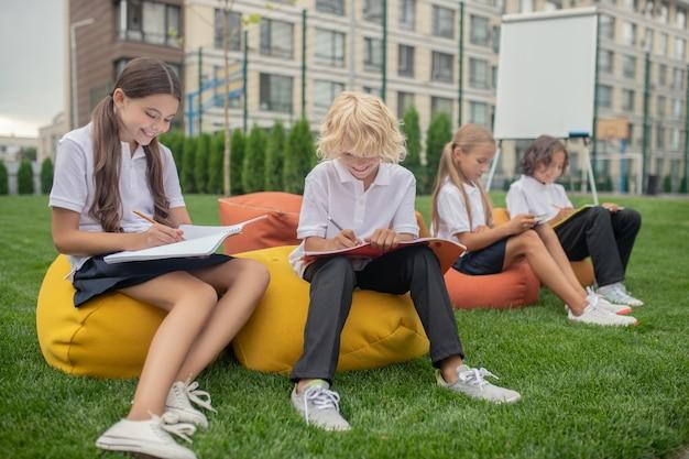 Wygląda na zajętego. dwoje dzieci pracuje razem na lekcji i wygląda na zajętego