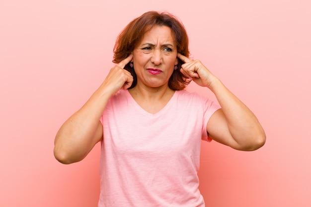 Wyglądając na złego, zestresowanego i zirytowanego, zakrywającego oboje uszu ogłuszającym hałasem, dźwiękiem lub głośną muzyką