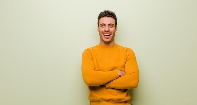 Wyglądający jak szczęśliwy, dumny i zadowolony wykonawca uśmiechnięty ze skrzyżowanymi rękami