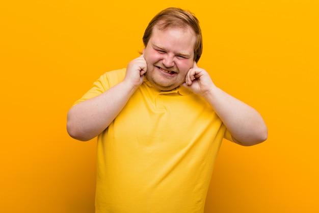 Wyglądający na wściekłego, zestresowanego i zirytowanego, obejmujący oboje uszu ogłuszającym hałasem, dźwiękiem lub głośną muzyką