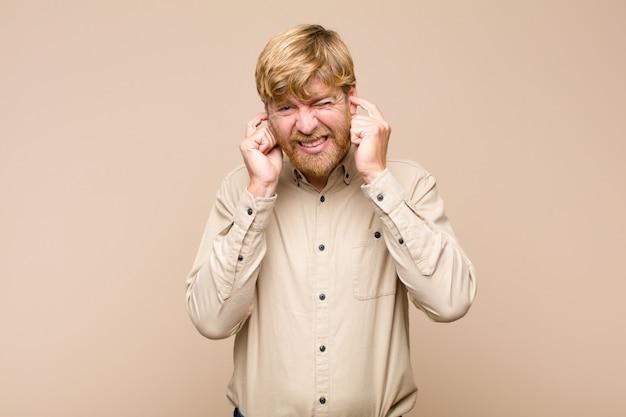 Wyglądający na wściekłego, zestresowanego i zirytowanego, zasłaniając uszy ogłuszającym hałasem, dźwiękiem lub głośną muzyką