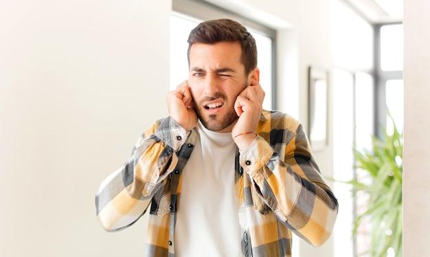 Wyglądający na zły, zestresowany i zirytowany, zakrywający oboje uszu ogłuszającym hałasem, dźwiękiem lub głośną muzyką