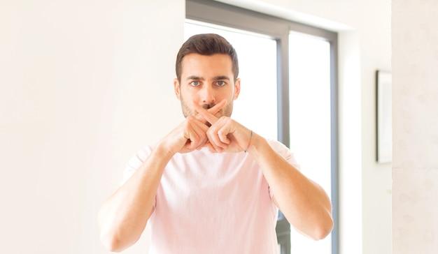 Wyglądający poważnie i niezadowolony z dwoma palcami skrzyżowanymi do góry w odrzuceniu, prosząc o ciszę