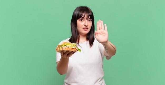 Wyglądający poważnie, surowo, niezadowolony i zły pokazując otwartą dłoń, robiąc gest zatrzymania