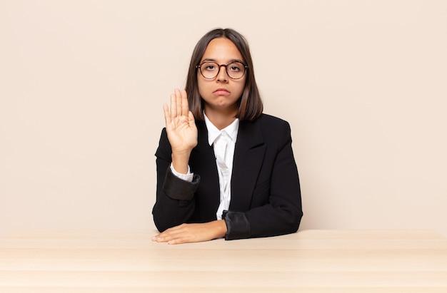 Wyglądający poważnie, surowo, niezadowolony i zły, pokazujący otwartą dłoń wykonujący gest zatrzymania