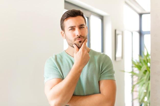 Wyglądający poważnie, zamyślony i nieufny, z jedną ręką skrzyżowaną i ręką na brodzie, opcje ważenia
