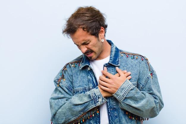 Wyglądający smutno, zraniony i ze złamanym sercem, trzymając obie ręce blisko serca, płacząc i czując się przygnębiony