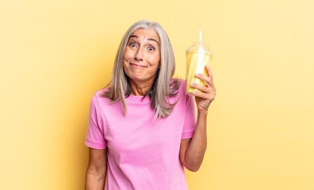 Wyglądam na szczęśliwą i mile zaskoczoną, podekscytowaną z zafascynowaną i zszokowaną miną, trzymającą koktajl mleczny