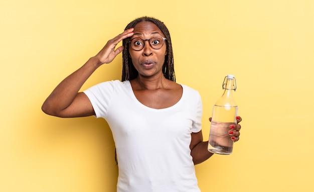 Wyglądam na szczęśliwą, zdziwioną i zdziwioną, uśmiechniętą i uświadamiając sobie niesamowite i niewiarygodnie dobre wieści. koncepcja butelki z wodą
