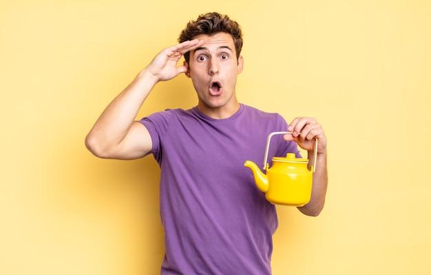Wyglądam na szczęśliwą, zdziwioną i zdziwioną, uśmiechniętą i uświadamiając sobie niesamowite i niewiarygodnie dobre wieści. koncepcja czajnika