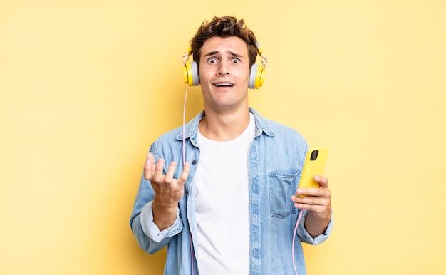 Wyglądam na zdesperowaną i sfrustrowaną, zestresowaną, nieszczęśliwą i zirytowaną, krzycząc i krzycząc. koncepcja słuchawek i smartfona