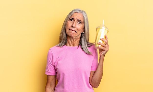 Wyglądam na zdziwioną i zdezorientowaną, przygryzając wargę nerwowym gestem, nie znając odpowiedzi na problem i trzymając koktajl mleczny