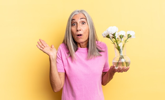 Wyglądam na zdziwioną i zszokowaną, z opuszczoną szczęką trzymająca przedmiot otwartą dłonią z boku trzymającego ozdobne kwiaty