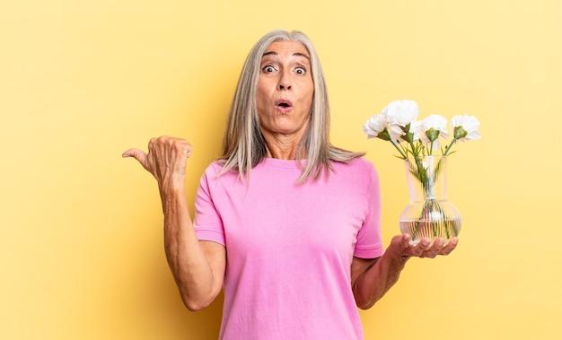 Wyglądam na zdziwioną z niedowierzaniem, wskazując na przedmiot z boku i mówiąc wow, niewiarygodne trzymanie ozdobnych kwiatów