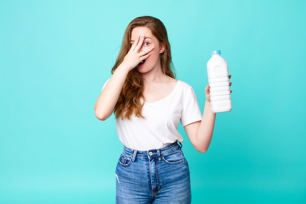 Wyglądam Na Zszokowaną, Przestraszoną Lub Przerażoną, Zakrywając Twarz Dłonią I Trzymając Butelkę Mleka Premium Zdjęcia