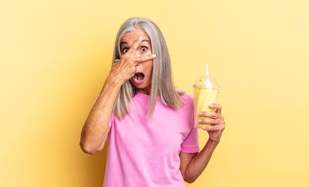 Wyglądam na zszokowaną, przestraszoną lub przerażoną, zakrywając twarz dłonią i zerkając między palcami i trzymając koktajl mleczny