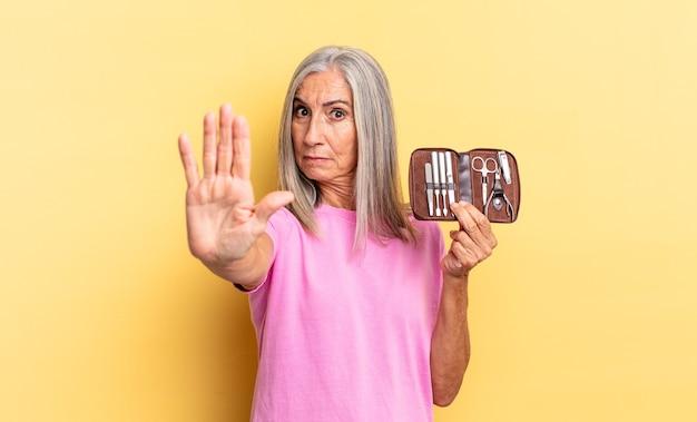Wyglądam poważnie, surowo, niezadowolony i wściekły pokazując otwartą dłoń, wykonując gest zatrzymania trzymający walizkę z narzędziami do paznokci