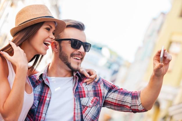 Wyglądamy świetnie! widok z boku szczęśliwa młoda kochająca para robi selfie stojąc razem na zewnątrz
