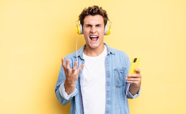 Wyglądasz na zły, zirytowany i sfrustrowany, krzycząc lub co jest z tobą nie tak. koncepcja słuchawek i smartfona