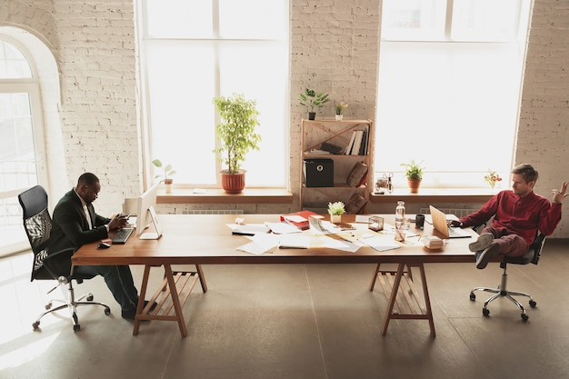 Wygłupia się przed swoim szefem. kaukaski pracownik, kierownik stara się pracować w biurze.