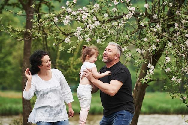 Wygłupiać się. wesoła para spędza miły weekend na świeżym powietrzu z wnuczką. dobra wiosenna pogoda