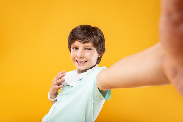 Wygłupiać. zadowolony, szczupły chłopiec w słuchawkach i robieniu selfie