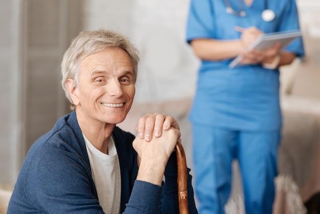 Wygoda dla osób starszych. kompetentny, opiekuńczy terapeuta lokalny, który udziela profesjonalnej pomocy w domu, podczas gdy pacjent wydaje się być zachwycony i siedzi na sofie
