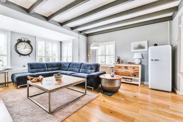 Wygodna kanapa i stoliki przy stylowej lampie w przestronnym salonie z pianinem i telewizorem w domu