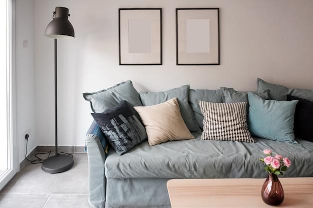 Wygodna klasyczna niebieska kanapa z poduszkami w prostym minimalistycznym mieszkaniu
