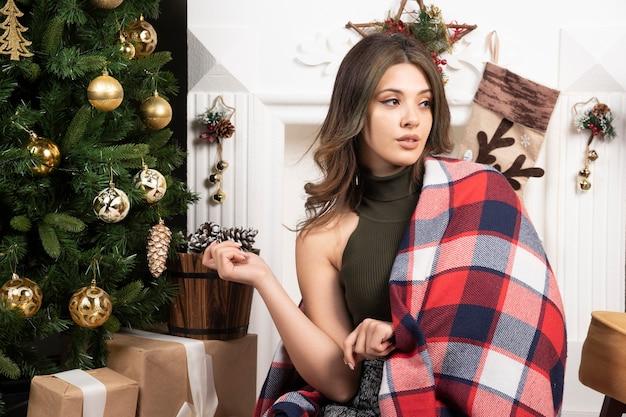 Wygodna kobieta w szaliku siedząca na białym dywanie przy kominku