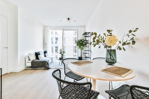 Wygodna miękka sofa i krzesło z poduszkami i pledem ustawione przy ścianie w nowoczesnym salonie z wykładziną i elementami dekoracyjnymi na małych stolikach stylizowanych na biało-szare kolory