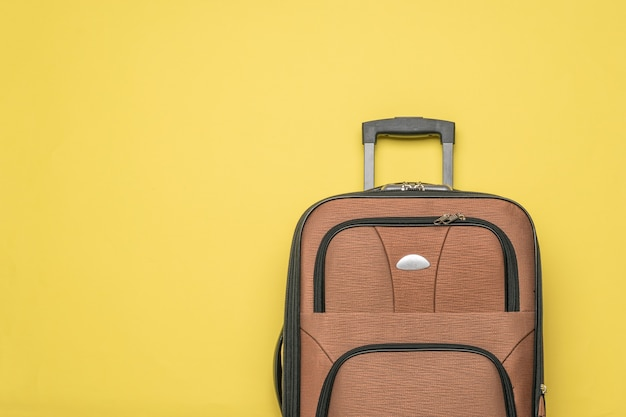 Wygodna walizka podróżna na żółtym tle. leżał płasko.