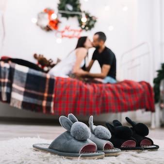 Wygodne buty domu na podłodze w pobliżu całuje para na łóżku