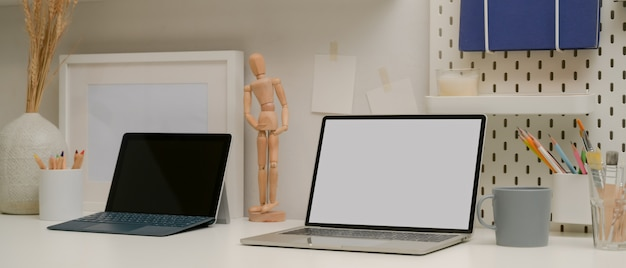 Wygodne designerskie miejsce do pracy z makietą laptopa, tabletem z klawiaturą, materiałami eksploatacyjnymi i dekoracjami