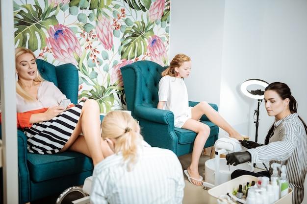 Wygodne fotele. matka i córka siedzą w wygodnych fotelach i cieszą się pedicure
