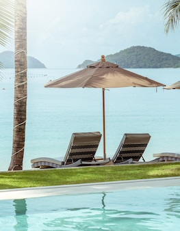 Wygodne krzesło przy basenie, nowoczesne krzesło, parasol i poduszka w kolorze brązowym.