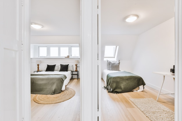 Wygodne łóżka znajdujące się za otwartymi drzwiami oddzielnych jasnych sypialni w jasnym mieszkaniu