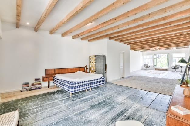 Wygodne łóżko z białym kocem w minimalistycznym przestronnym pokoju domu z drewnianymi belkami na suficie